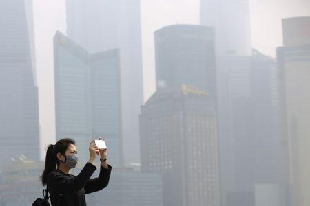 A woman wears a mask as she takes pictures on the Bund on a hazy day in Shanghai