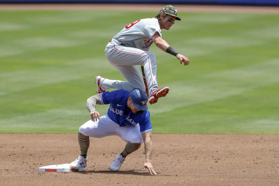 Philadelphia Phillies shortstop Nick Maton, top, jumps over Toronto Blue Jays' Randal Grichuk to complete a throw for a double play against Blue Jays' Rowdy Tellez during the first inning of a baseball game Sunday, May 16, 2021, in Dunedin, Fla. (AP Photo/Mike Carlson)