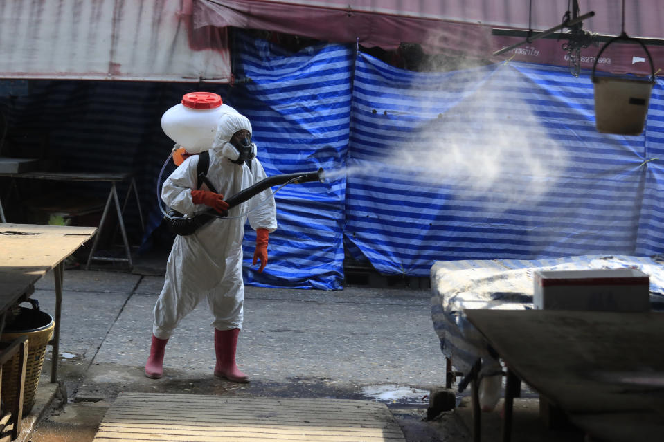 A worker sprays disinfectant as a precaution against the coronavirus at Klong Toey market in Bangkok, Thailand, Friday, Jan. 15, 2021. The market was temporarily closed after a person there tested positive for the coronavirus earlier this week. Thailand's government recently announced new measures, including partial lockdowns with strict travel restrictions in some areas, after a surge of coronavirus cases. Schools, bars, gambling parlors and other public gathering places were closed. (AP Photo/Sakchai Lalit)