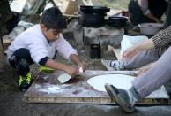 An Afghan migrant child prepares lunch with his mother at a makeshift camp near Velika Kladusa