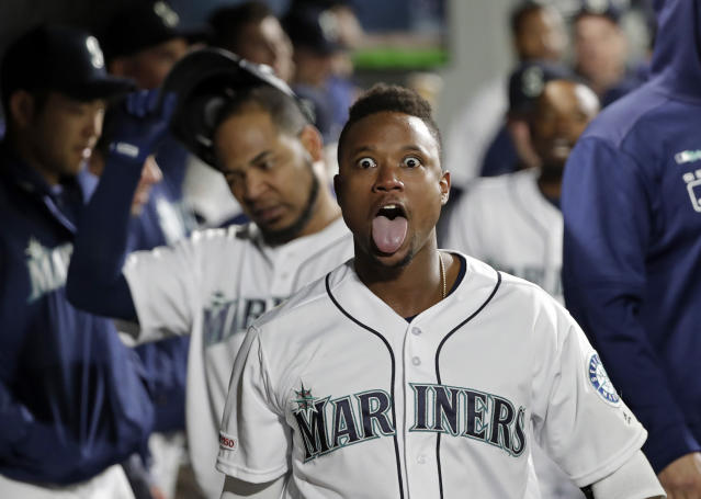 Seattle Mariners' Tim Beckham mugs for photographers from in the dugout after hitting a two-run home run against the Texas Rangers in the sixth inning of a baseball game Thursday, April 25, 2019, in Seattle. (AP Photo/Elaine Thompson)