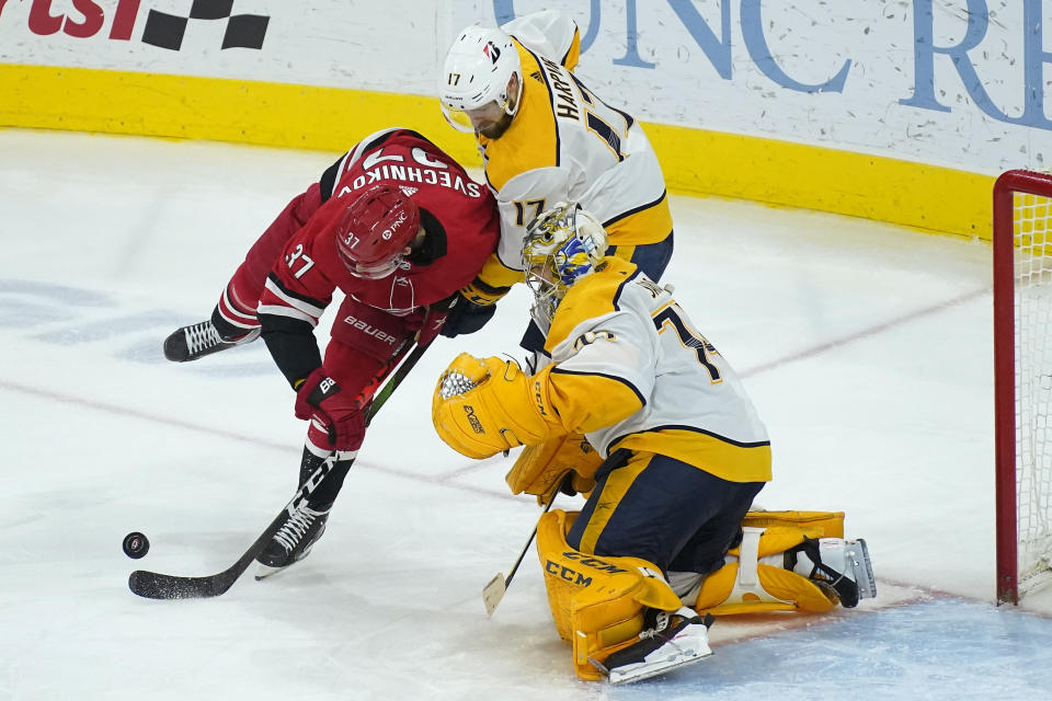 Carolina Hurricanes right wing Andrei Svechnikov (37) tries to score against Nashville Predators goaltender Juuse Saros (74) while defenseman Ben Harpur (17) defends during the third period of an NHL hockey game in Raleigh, N.C., Saturday, April 17, 2021. (AP Photo/Gerry Broome)