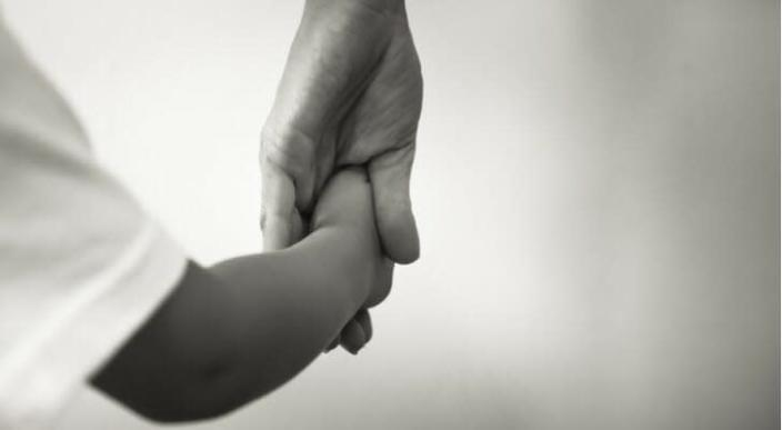 Child holding hands with adoptive parent