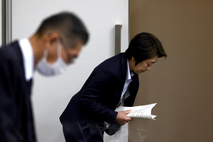 President of the Tokyo 2020 Olympics Organizing Committee Seiko Hashimoto, right, bows as she leaves after her speech at a press briefing on the operation and media coverage of Tokyo 2020 Olympic Torch Relay in Tokyo Thursday, Feb. 25, 2021. (Behrouz Mehri/Pool Photo via AP)