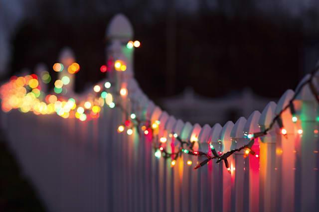 a string of multi-colored christmas lights are strung across a white plastic fence.  their reflection is cast upon the reflectiv