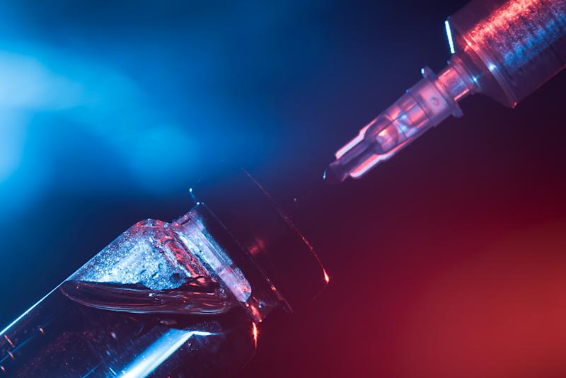 A glass medical bottle with a vaccine and a disposable syringe in color light. A conceptual photo about the danger of viral diseases