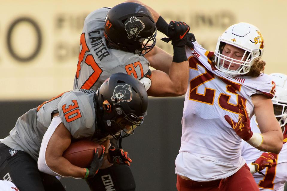 File-This Oct. 24, 2020, file photo shows Oklahoma State lineman Logan Carter (87) grabbing the jersey of Iowa State linebacker Mike Rose (23) while Oklahoma State running back Chuba Hubbard (30) attempts to sneak by during an NCAA college football game in Stillwater, Okla. Rose, like everybody else in college football, had no idea last spring if there would be a season. Iowa State's junior linebacker wanted to be ready just in case, so day in and day out for three months he went to his high school in the Cleveland suburb of Brecksville, Ohio, to do workouts prescribed by the Cyclones' new strength staff. (AP Photo/Brody Schmidt, File)