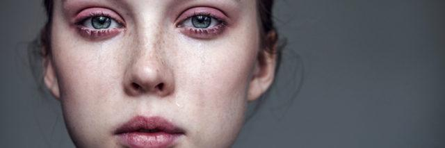 up close photo of a woman crying with tears streaming down her face and a straight face