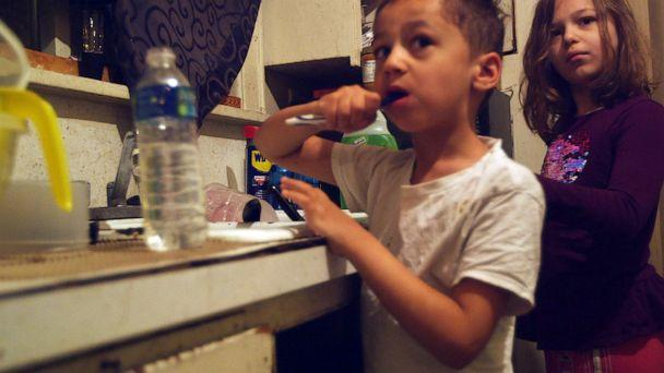 PHOTO: Gabriel and Nala Uherek brush their teeth using bottled water in their family's home in Flint, Mich. (Janet Weinstein/ABC News)