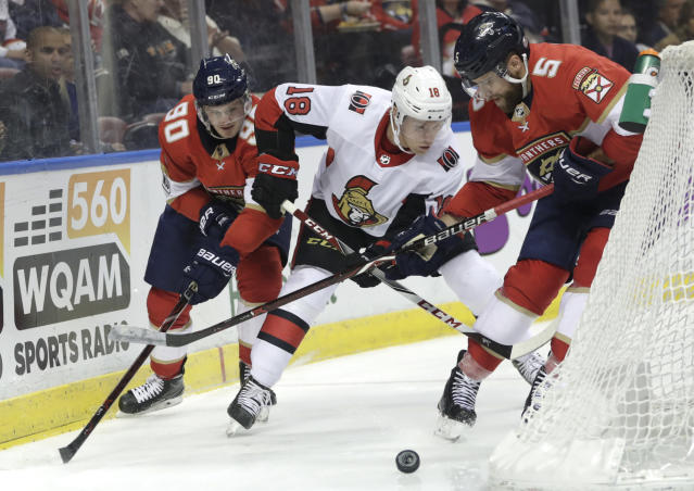 Florida Panthers' Jared McCann (90) and Aaron Ekblad (5) go for the puck against Ottawa Senators' Ryan Dzingel (18) during the second period of an NHL hockey game, Monday, March 12, 2018, in Sunrise, Fla. (AP Photo/Lynne Sladky)