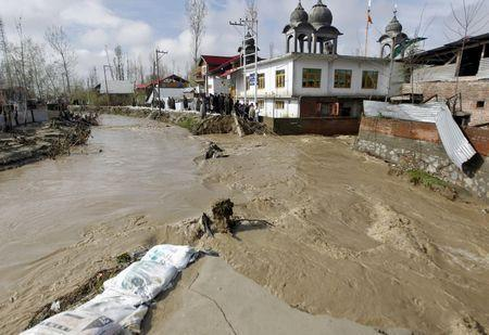 People watch as water flows from a broken embankment of a stream after incessant rains in Srinagar March 30, 2015. REUTERS/Danish Ismail