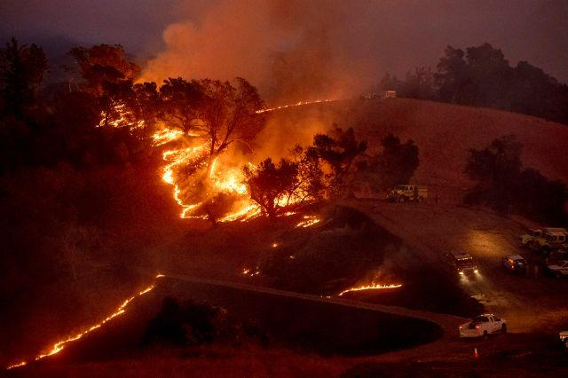 Flames from a backfire, lit by firefighters to slow the spread of the Kincade Fire, burn a hillsid Sonoma County near Geyservillle on Oct. 26.