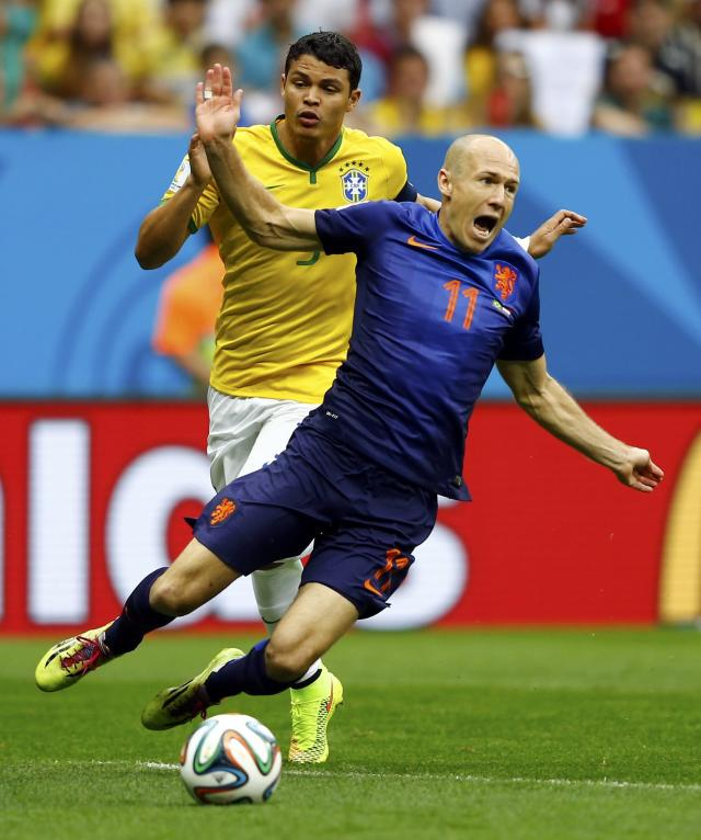 Brazil's Thiago Silva (L) fouls Arjen Robben of the Netherlands to concede a penalty during their 2014 World Cup third-place playoff at the Brasilia national stadium in Brasilia July 12, 2014. REUTERS/Dominic Ebenbichler (BRAZIL - Tags: SOCCER SPORT WORLD CUP TPX IMAGES OF THE DAY)
