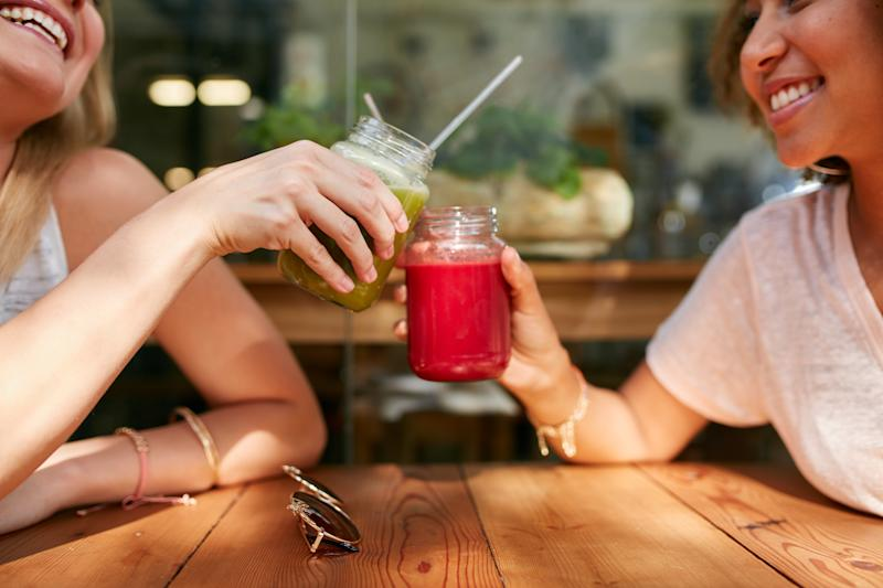 Close up shot of female friends toasting juice glasses at sidewalk cafe. (PHOTO: Getty Images)