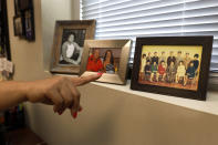 """Tianna Cervantez, Assistant Dean of Diversity and Inclusion at Knox College, points out a framed photograph of her family in her office, Wednesday, June 16, 2021, in Galesburg, Il. Cervantez, a member of the school board and legacy of the Mexican railroad camps, saw in people she and her family had known for generations, the angry opposition to a resolution acknowledging """"institutionalized racism"""" in policing, hiring, public health and other facets of community life. (AP Photo/Shafkat Anowar)"""