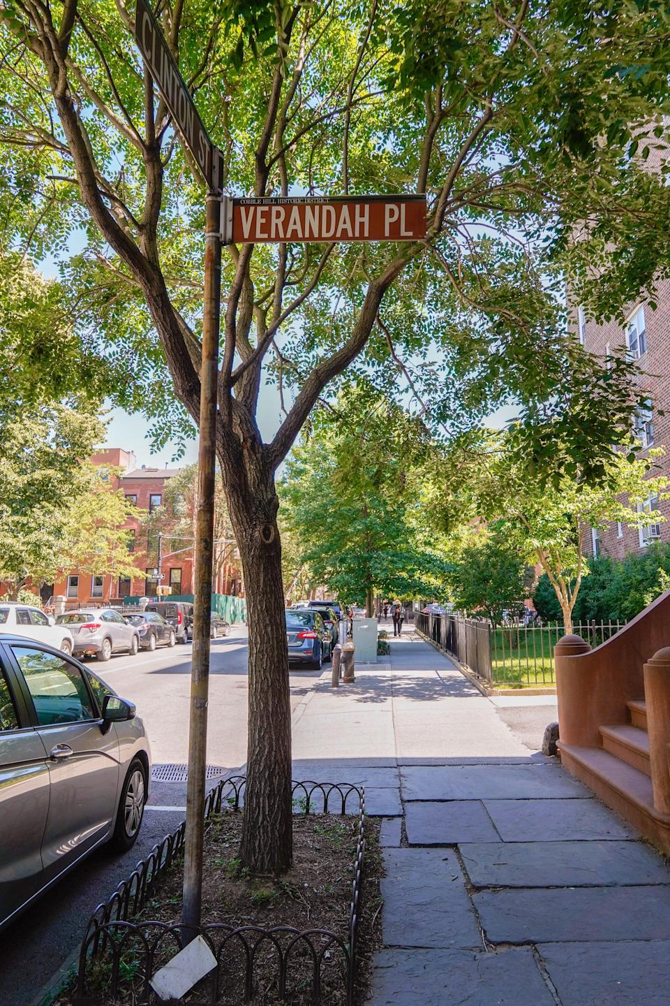 Verandah place sign in front of a tree on a sidewalk