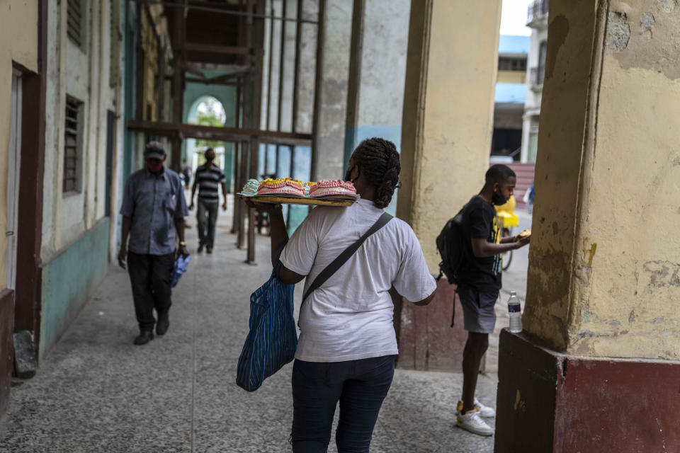 A woman walks down the street carrying a tray of cakes in Havana, Cuba, Monday, July 26, 2021 (AP Photo/Eliana Aponte)