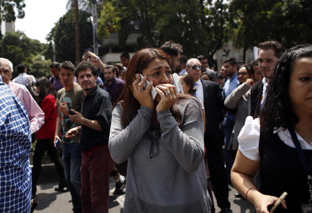 <p>A woman speaks on her cell phone as people evacuated from office building gather in Reforma Avenue after an earthquake in Mexico City, Tuesday Sept. 19, 2017. A powerful earthquake jolted central Mexico on Tuesday, causing buildings to sway sickeningly in the capital on the anniversary of a 1985 quake that did major damage.(Photo: Rebecca Blackwell/AP) </p>