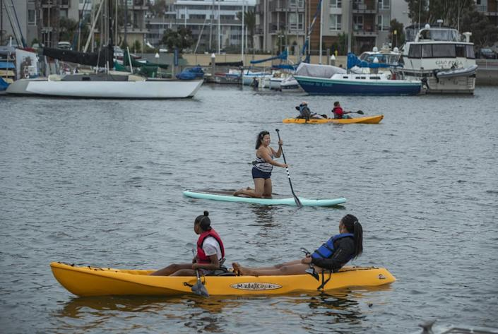 People paddle along in their kayaks and paddle board, center, during a visit to Marina Beach, also known as Mother's Beach