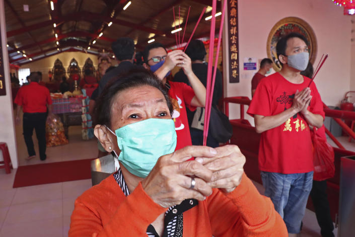 Ethnic Chinese worshippers wearing face masks to help curb the spread of coronavirus outbreak pray during the Lunar New Year celebrations at a temple in the China Town area of Jakarta, Indonesia, Friday, Feb.12, 2021. (AP Photo/Tatan Syuflana)