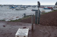 Discarded sandals and a sign knocked-over following a heavy storm in Shaldon, Devon, England, Saturday July 24, 2021. (AP Photo/Tony Hicks)