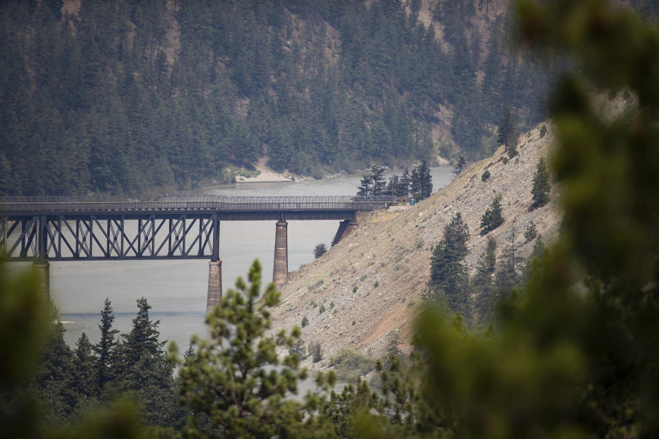 A rail bridge spans the Fraser River as a wildfire burns in Lytton, British Columbia, Friday, July 2, 2021. Officials on Friday hunted for any missing residents of the British Columbia town destroyed by wildfire as Canadian Prime Minister Justin Trudeau offered federal assistance. (Darryl Dyck/The Canadian Press via AP)