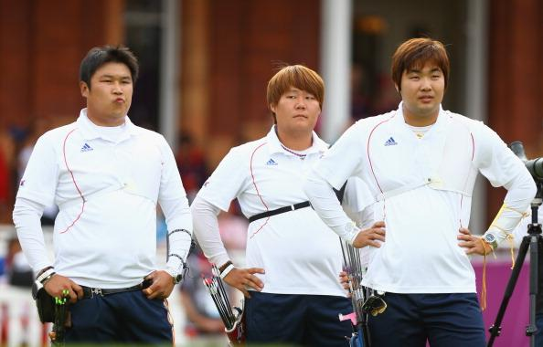 LONDON, ENGLAND - JULY 28:  (L-R) Jinhyek Oh, Bubmin Kim and Donghyun Im of Korea look on after defeat in the Men's Team Archery semi final between the United States and Korea on Day 1 of the London 2012 Olympic Games at Lord's Cricket Ground on July 28, 2012 in London, England.  (Photo by Paul Gilham/Getty Images)