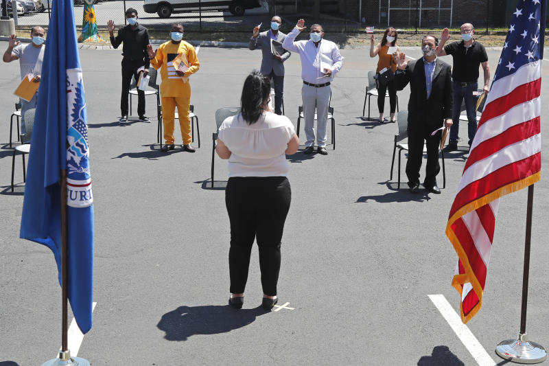 New citizens are sworn in while observing social distancing, outside the U.S. Citizenship and Immigration Services building, Thursday, June 4, 2020, in Lawrence, Mass. The federal agency is resuming services in many cities across the country after being shuttered for more than two months because of the coronavirus pandemic. (AP Photo/Elise Amendola)