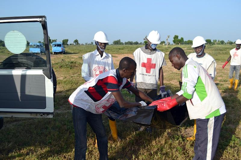 Red Cross officials in Maiduguri on October 16, 2015 remove a dead body at the scene of a blast (AFP Photo/Stringer)