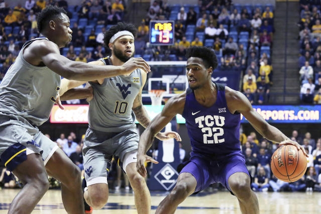 TCU guard RJ Nembhard (22) is defended by West Virginia forward Oscar Tshiebwe (34) and guard Jermaine Haley (10) during the first half of an NCAA college basketball game Tuesday, Jan. 14, 2020, in Morgantown, W.Va. (AP Photo/Kathleen Batten)