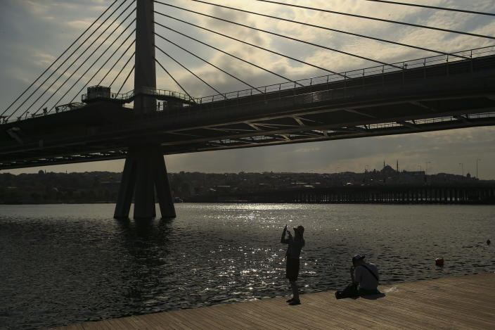 A woman takes a picture by the Golden Horn, leading to the Bosphorus Strait separating Europe and Asia, in Istanbul, Friday, May 14, 2021.Turkey is in the final days of a full coronavirus lockdown and the government has ordered people to stay home and businesses to close amid a huge surge in new daily infections. But millions of workers are exempt and so are foreign tourists. Turkey is courting international tourists during an economic downturn and needs the foreign currencies that tourism brings to help the economy as the Turkish lira continues to sink. (AP Photo/Emrah Gurel)