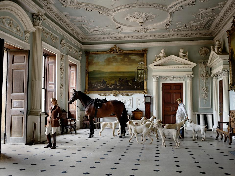 Gathered in Badminton's North Hall, Georgia Beaufort, the Duchess of Beaufort, and Matt Ramsden, Master of the Duke of Beaufort's Hunt, with horse and hounds.