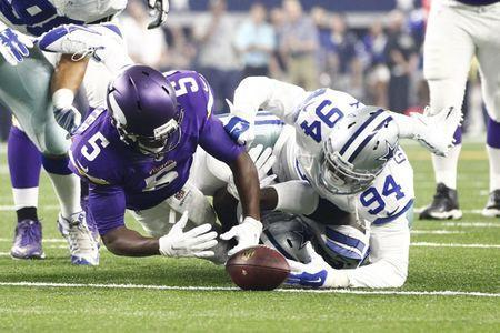 Aug 29, 2015; Arlington, TX, USA; Minnesota Vikings quarterback Teddy Bridgewater (5) fumbles the ball against Dallas Cowboys defensive end Randy Gregory (94) in the first quarter at AT&T Stadium. Mandatory Credit: Tim Heitman-USA TODAY Sports / Reuters Picture Supplied by Action Images