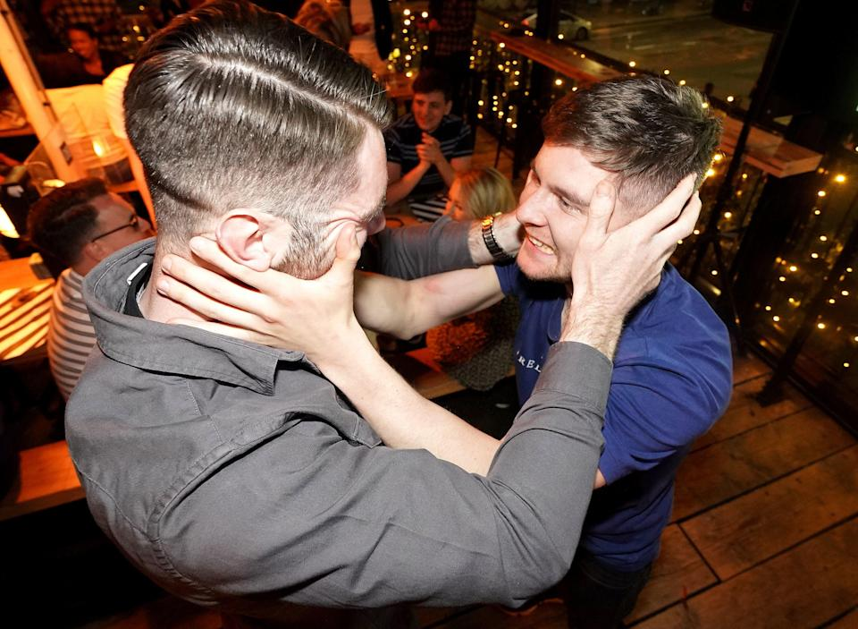 Two men celebrate at Boxpark in Shoreditch (PA)