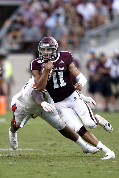 Texas A&M quarterback Kellen Mond (11) runs away from an Auburn defender during the second half of an NCAA college football game, Saturday, Sept. 21, 2019, in College Station, Texas. (AP Photo/Sam Craft)