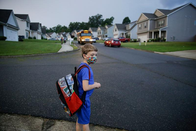 A 7-year-old boy wearing a mask waits at the bus stop on Aug. 3, the first day of school in Dallas, Georgia. (Photo: AP Photo/Brynn Anderson)