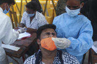 A health worker takes a nasal swab sample of a man to test for COVID-19 in Mumbai, India, Monday, April 5, 2021. India reported its biggest single-day spike in confirmed coronavirus cases since the pandemic began Monday, and officials in the hard-hit state home to Mumbai are returning to the closure of some businesses and places of worship in a bid to slow the spread. (AP Photo/Rafiq Maqbool)