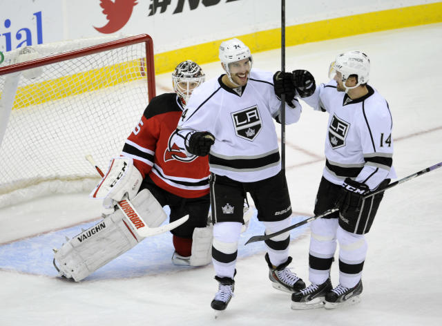 Los Angeles Kings' Dwight King celebrates his goal with Justin Williams, right, as New Jersey Devils goaltender Cory Schneider, left, reacts during the third period of an NHL hockey game Friday, Nov. 15, 2013, in Newark, N.J. The Kings defeated the Devils 2-0. (AP Photo/Bill Kostroun)