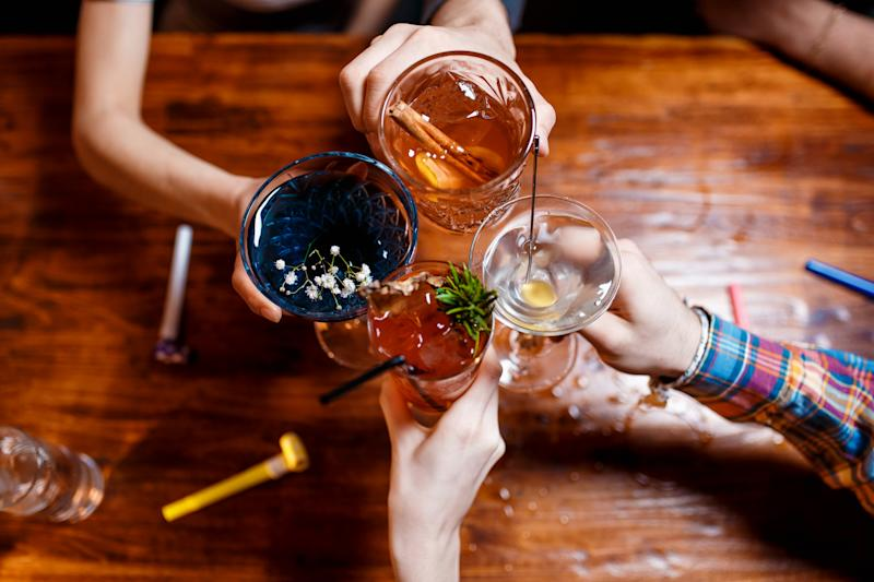 friends clinking by glasses with various alcoholic cocktails at table,close up top view