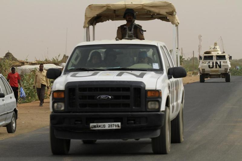 African Union-United Nations Mission in Darfur vehicles drive on a road in El-Fasher, north Darfur, on April 28, 2014