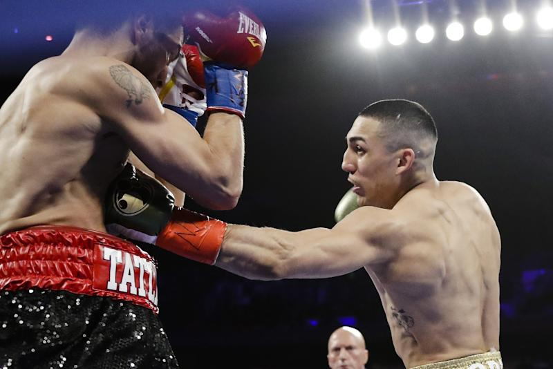 FILE - In this Saturday, April 20, 2019, file photo, Teofimo Lopez, right, punches Finland's Edis Tatli during the first round of a NABF lightweight championship boxing match in New York. In ordinary times Vasiliy Lomachenko and Teofimo Lopez would be the fight of the fall, a lightweight title match about as compelling as it gets in the boxing world these days. Instead of a big crowd, the only fans at the MGM Grand conference center will be a few hundred sponsors and first responders with special invites. And, instead of pay-per-view, the fight will be televised live on ESPN, guaranteeing a larger audience than a pay-per-view even if the money isn't nearly the same. (AP Photo/Frank Franklin II, File)