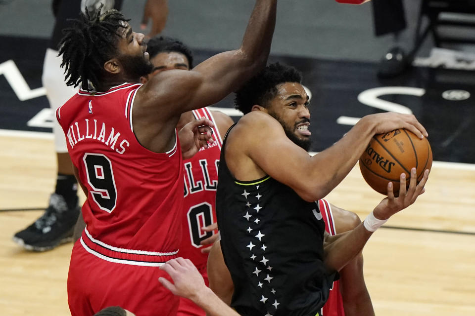 Minnesota Timberwolves center Karl-Anthony Towns, right, rebounds the ball against Chicago Bulls forward Patrick Williams during the second half of an NBA basketball game in Chicago, Wednesday, Feb. 24, 2021. (AP Photo/Nam Y. Huh)
