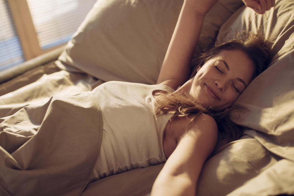 Close up of a woman stretching on a bed