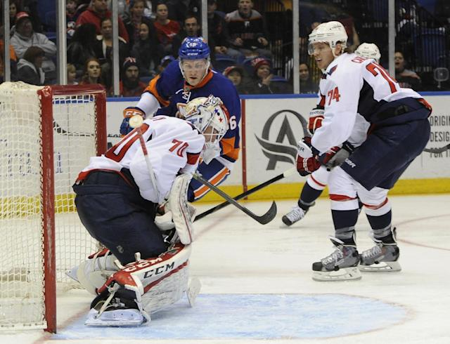 New York Islanders' John Persson (56) shoots the puck past Washington Capitals goalie Braden Holtby (70) as Capitals' John Carlson (74) looks on in the second period of an NHL hockey game, Saturday, April 5, 2014, in Uniondale, N.Y. (AP Photo/Kathy Kmonicek)