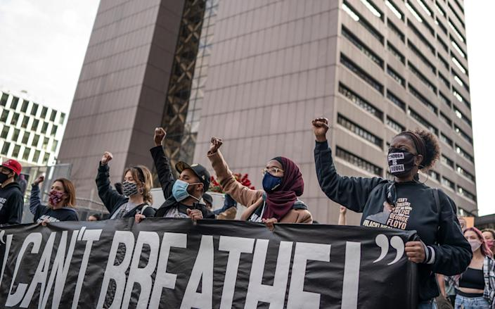 Demonstrators march past the Hennepin County Government Center on March 7, a day before jury selection was set to begin in the trial of former Minneapolis police officer Derek Chauvin, who is accused of killing George Floyd in Minneapolis.