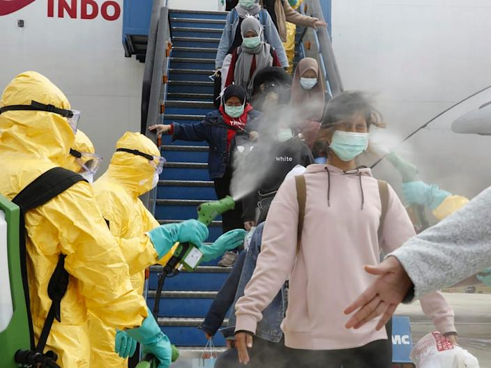 Indonesians arriving from Wuhan, China, are sprayed with antiseptic at Hang Nadim Airport in Batam on February 2.