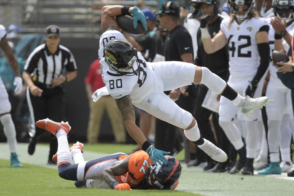 Jacksonville Jaguars tight end James O'Shaughnessy (80) is knocked out of bounds by Denver Broncos safety Kareem Jackson (22) during the first half of an NFL football game, Sunday, Sept. 19, 2021, in Jacksonville, Fla. (AP Photo/Phelan M. Ebenhack)
