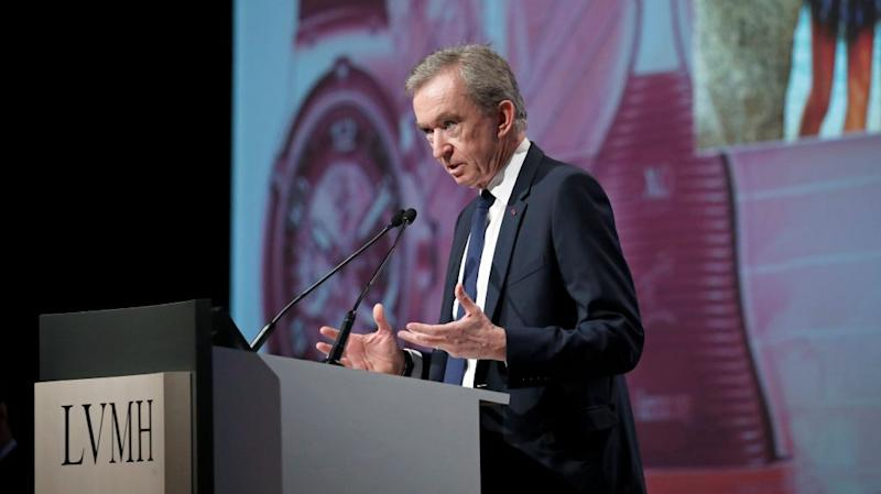 Bernard Arnault speaks at a podium with LVMH on the front