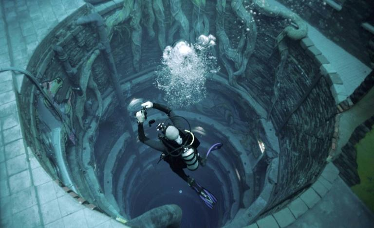 A diver experiences Deep Dive Dubai, the deepest swimming pool in the world