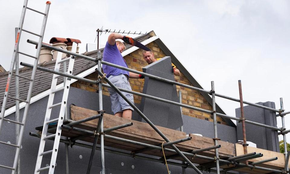 Workers attach foam wall-insulation panels to a terraced house.
